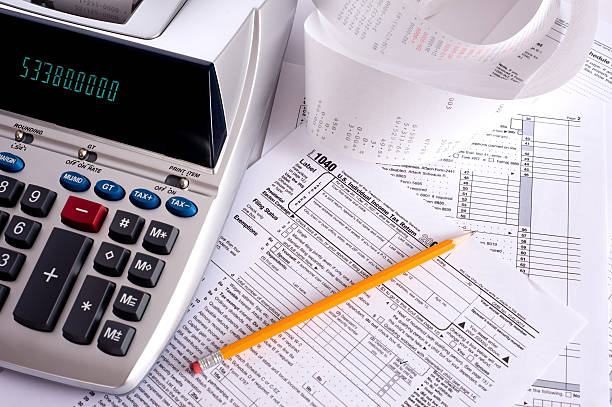 Adding Machine with tax forms An adding machine or calculator with adding machine tape or paper and tax forms receipt stock pictures, royalty-free photos & images