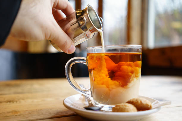 Adding milk top on English Tea stock photo