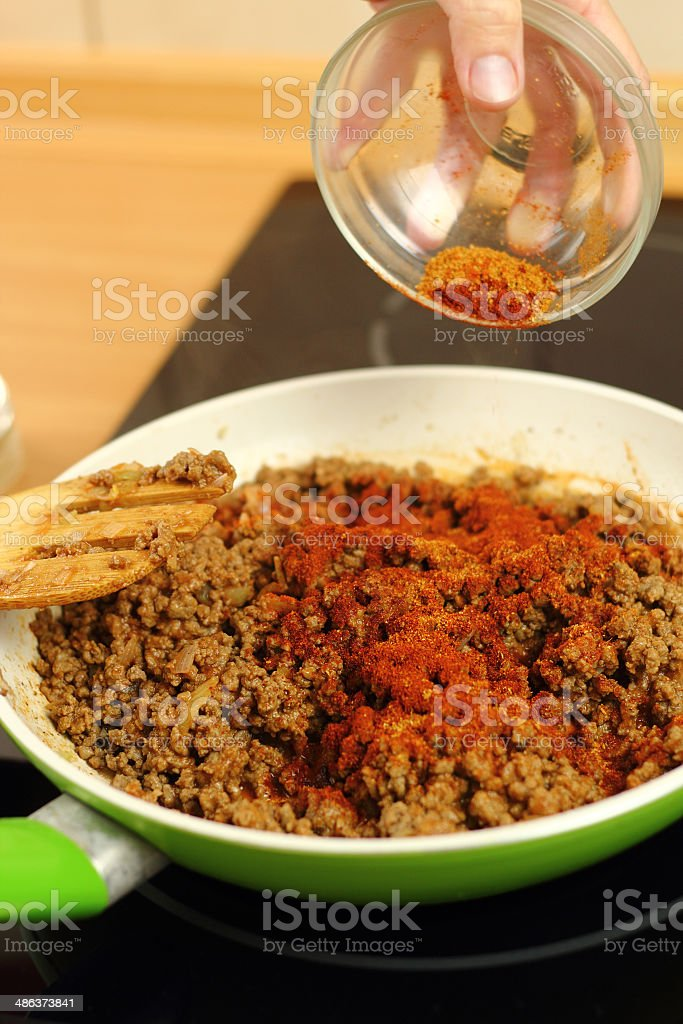 Adding mix spices into ground beef royalty-free stock photo
