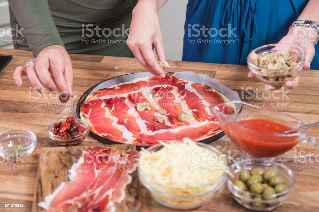 Hinzufügen von Pilzen beim Pizzabacken. – Foto