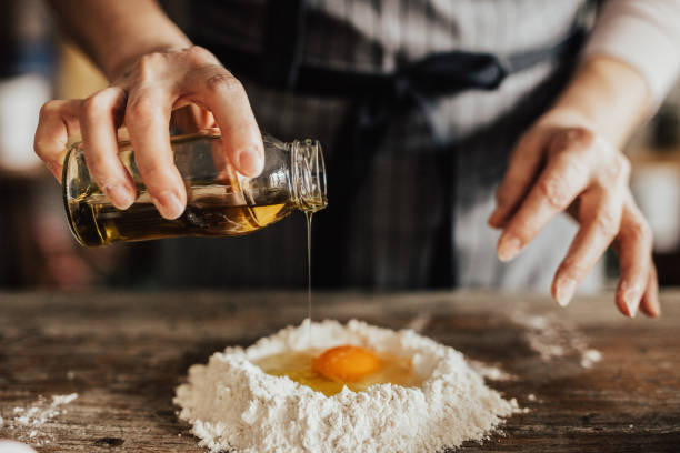 Adding oil to the egg and flour stock photo