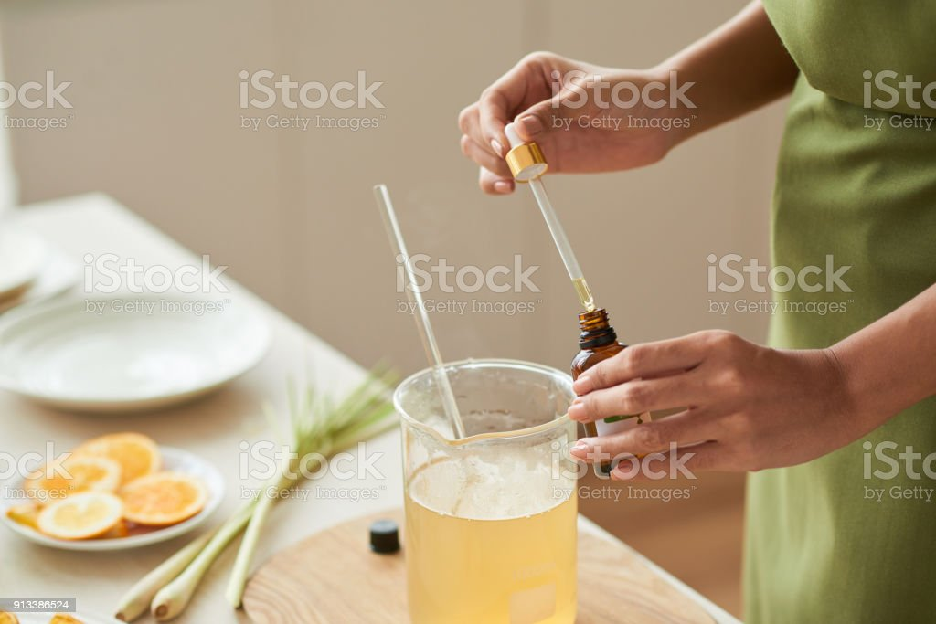 Adding oils into soap mixture stock photo
