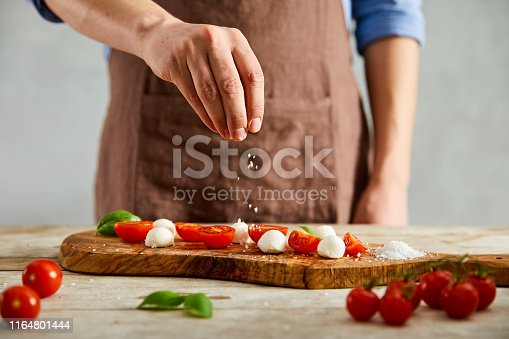 Male cook is adding a pinch of salt on tomatoes, mozzarella and basil on a olive cutting board.