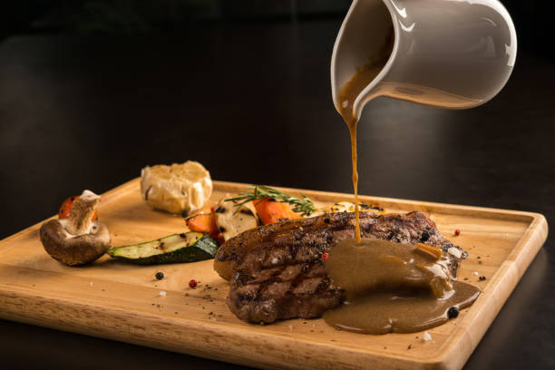 Adding sauce Gravy pouring over grilled seasoned meat, isolated on black savory sauce stock pictures, royalty-free photos & images