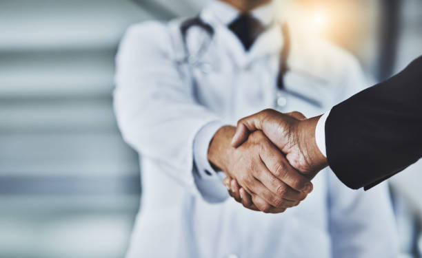 Adding the corporate factor to healthcare Cropped shot of a doctor shaking hands with a businessman in a hospital salesman stock pictures, royalty-free photos & images