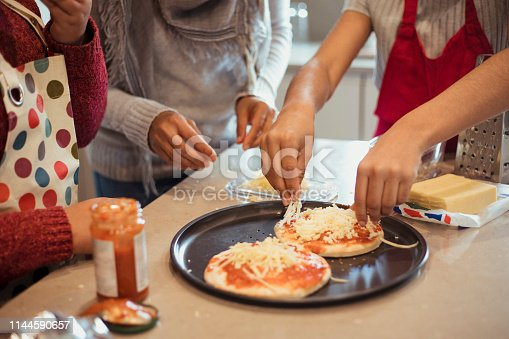 A close-up of a family including a mother, daughter and son, preparing pizzas for dinner by adding the cheese on top.
