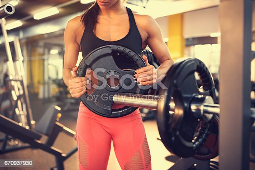 670937518istockphoto Adding weights on barbell, concept 670937930