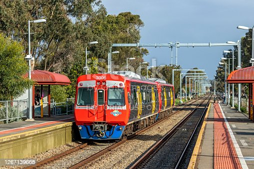 Adelaide, Australia - August 19, 2020: an Adelaide Metro diesel commuter train departs Dudley Park Railway Station with newly-erected overhead wire stanchions for the Gawler Line Electrification Project clearly visible.