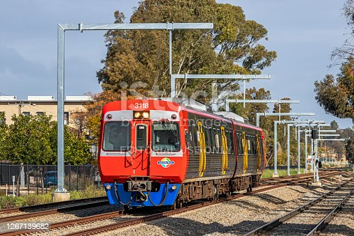 Adelaide, Australia - August 19, 2020: an Adelaide Metro diesel commuter train passes by under newly-erected overhead wire stanchions for the Gawler Line Electrification Project.
