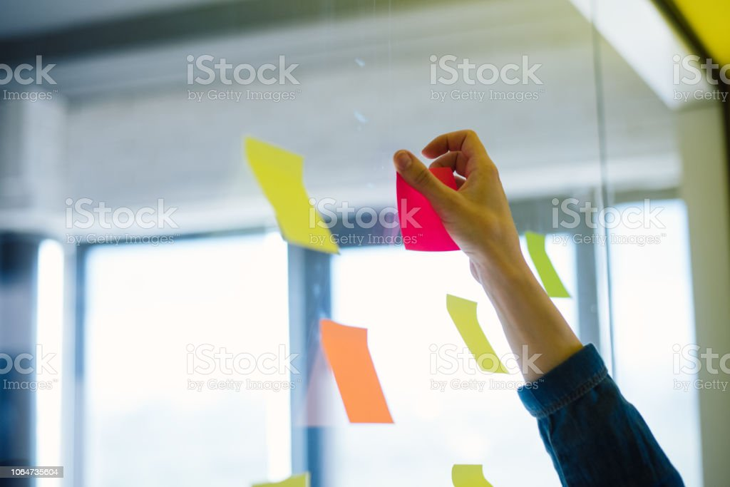 Young girl and a guy are putting sticky notes