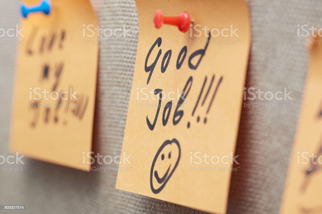 Nota adhesiva con texto de buen trabajo en un tablón de corcho - foto de stock
