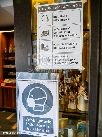 Rome, Italy, October 19 -- Adhesive notices indicate at the entrance of a shop the rules and restrictions to be respected due to the Covid-19 health crisis, such as the mandatory use of a health mask, maintaining social distance, limiting access for people with a maximum of two people, sanitize hands and use medical gloves.