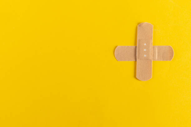 Adhesive Plaster Adhesive plaster on the yellow background. adhesive bandage stock pictures, royalty-free photos & images
