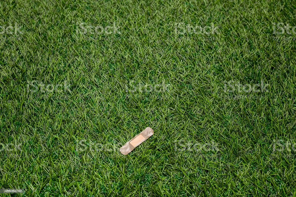 Adhesive plaster sticked to green grass stock photo