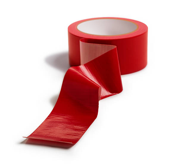 Adhesive Red Tape Isolated on White This is a photo taken in the studio of a roll of red duct tape isolated on a white background. The focus is on the front of the tape and falls off in the back. bureaucracy stock pictures, royalty-free photos & images