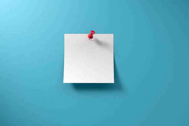 Adhesive Sticky Note and Thumbtack on Blue Background stock photo