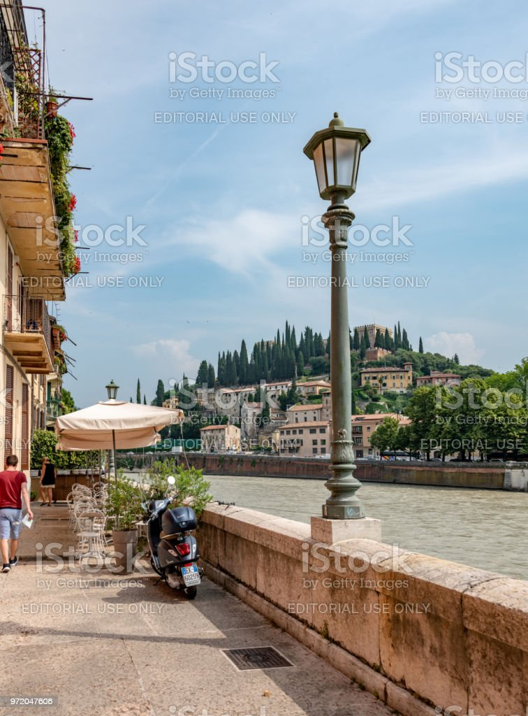 Adige River bank with cafe seating and moped in Verona, Italy stock photo