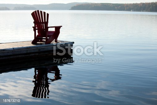 An adirondack chair by a lake. Image taken in the Muskoka region of Ontario, Canada. This region is known for being cottage country. Towns such as Gravenhurst, Deerhurst, Barrie, and the Algonquin are prime summer holiday destinations.