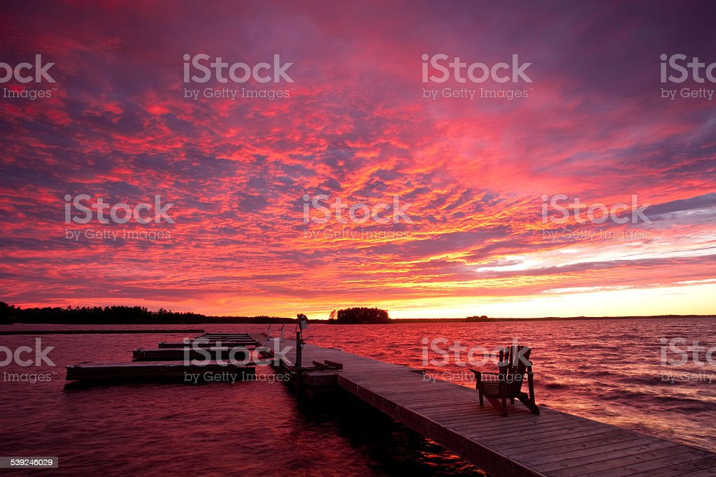 Adirondack Chair on a Dock By Lake With Beautiful Sunset stock photo