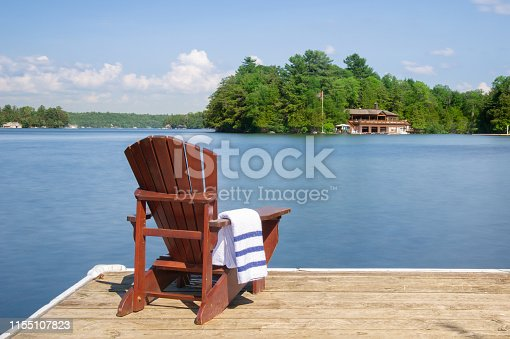 Adirondack chair on a wooden dock on a calm lake in Muskoka, Ontario Canada. A cottage nestled between trees is visible across the water. A white towel in folded on the arm chair.