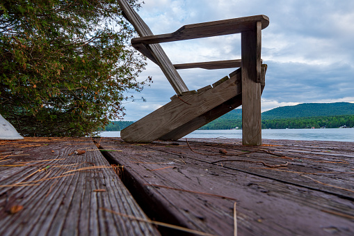 Three Adirondack Chairs On A Wooden Dock Stock Photo