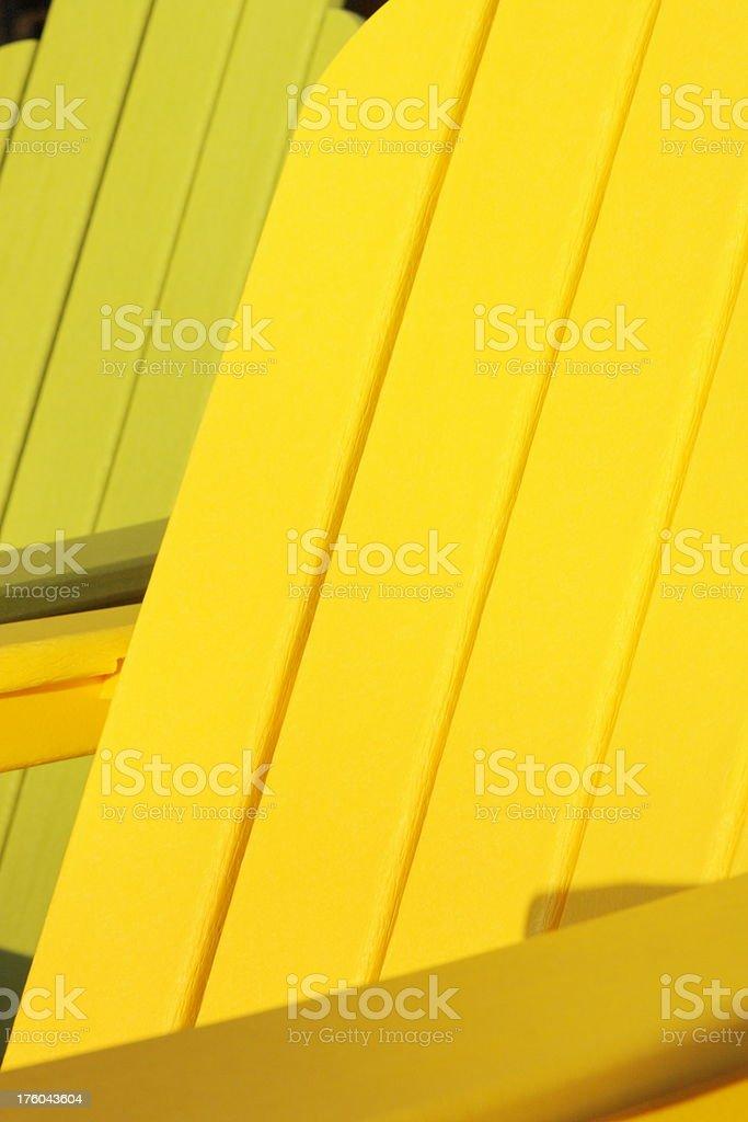 Adirondack chairs in yellow green plastic under sunset lighting.