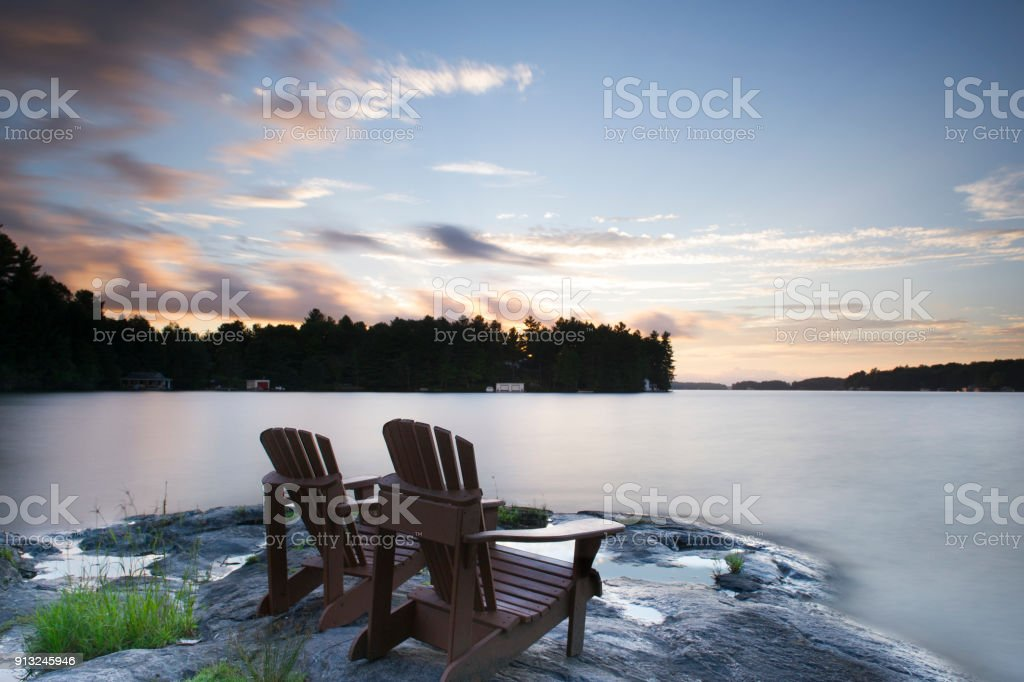 Adirondack chairs facing a lake at sunset stock photo