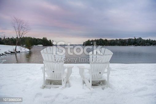 Adirondack chairs covered in snow facing a lake at sunset in Muskoka, Canada