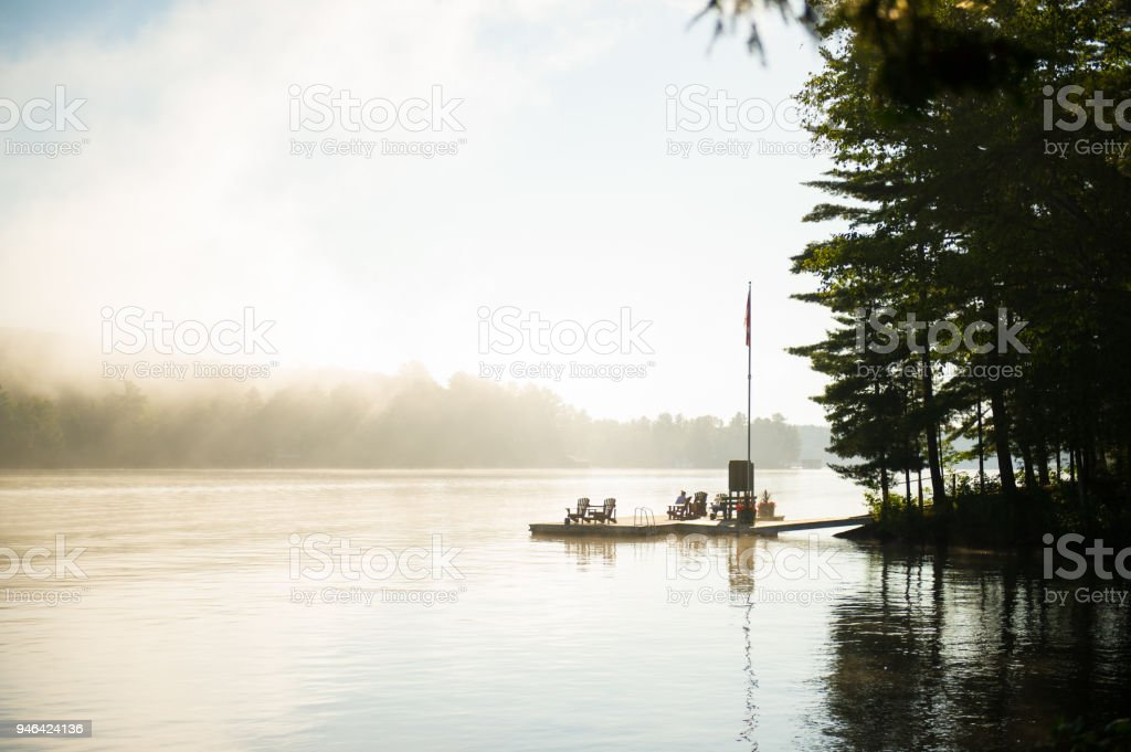 Red Adirondack Chair On A Wooden Dock Stock Photo