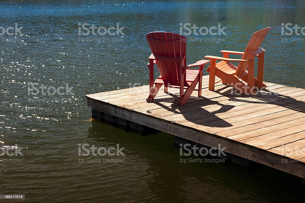 Adirondack chairs on a dock stock photo