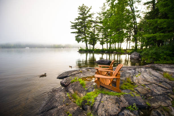 Adirondack chairs on a rock formation early morning Adirondack chairs on a rock formation facing a calm lake. Ducks are in the water. The morning mist is covering part of the lake. holiday villa stock pictures, royalty-free photos & images