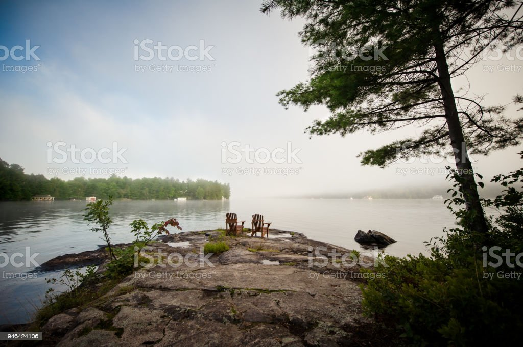 Adirondack chairs on a rock formation stock photo