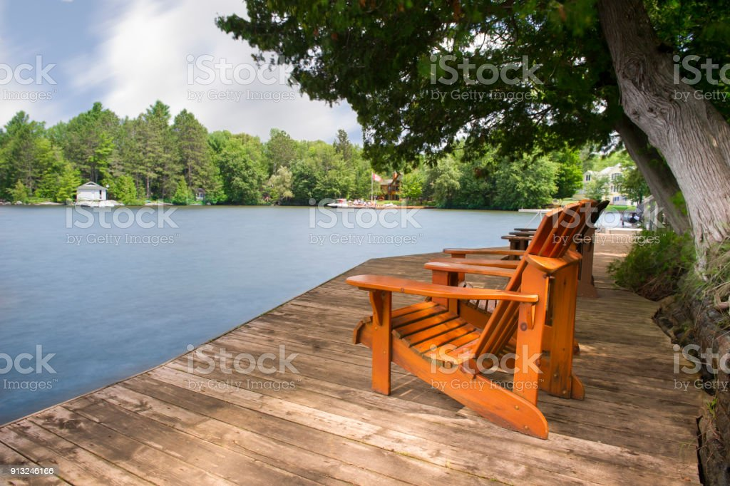 Adirondack chairs on a wood dock facing a lake stock photo