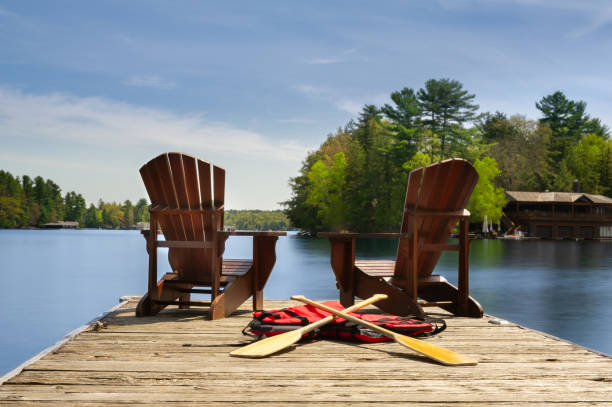 Adirondack chairs on a wooden dock facing ta calm lake Two Adirondack chairs on a wooden dock facing the blue water of a lake in Muskoka, Ontario Canada. Canoe paddles and life jackets are on the dock. A cottage nestled between green trees is visible. lake stock pictures, royalty-free photos & images