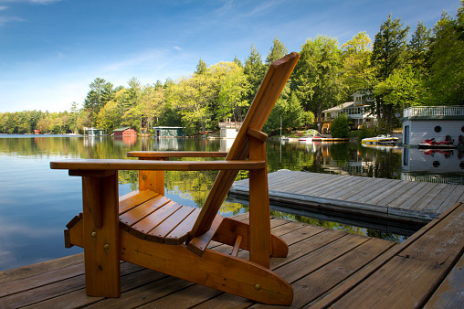 Two red adirondack chairs on floating dock on river Stock