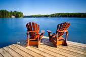 Adirondack chairs on a wooden dock on a calm lake in Muskoka, Ontario Canada. Cottages nestled between trees are visible across the water.
