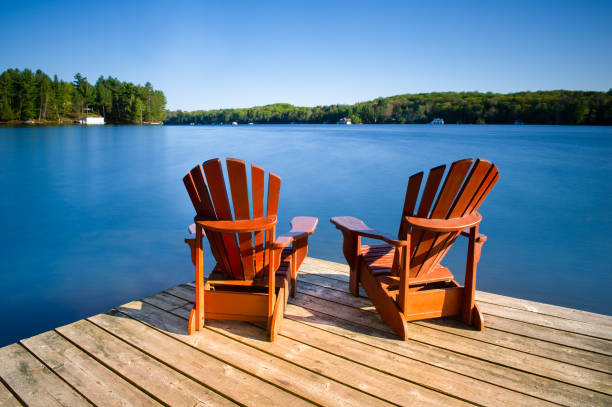 Adirondack chairs on a wooden pier Adirondack chairs on a wooden dock on a calm lake in Muskoka, Ontario Canada. Cottages nestled between trees are visible across the water. lake stock pictures, royalty-free photos & images