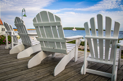 Adirondack Chairs On A Wooden Porch Overlooking A Lake