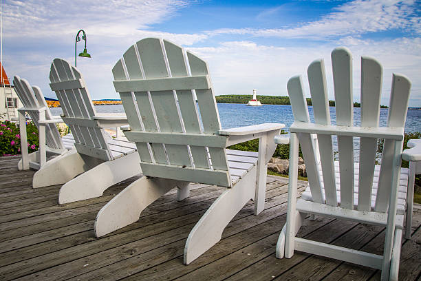 adirondack chairs on a wooden porch overlooking a lake - mackinac island stock photos and pictures
