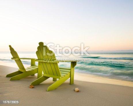 Two beach chairs on the beach facing a still horizon. Horizontal shot.