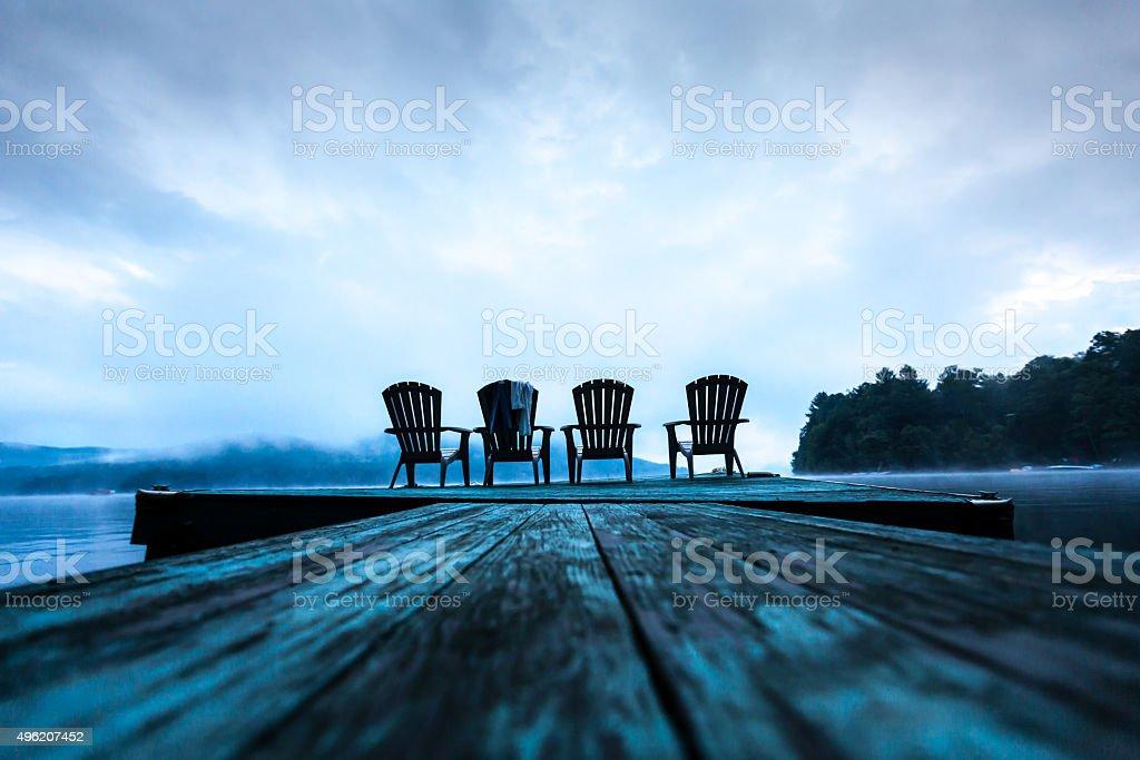 Adirondack chairs on dock stock photo