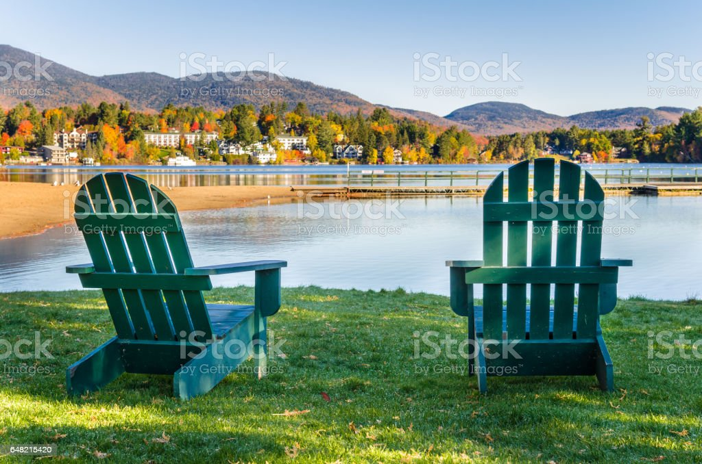 Adirondack Chairs on the Shore of Lake on a Clear Fall Morning stock photo