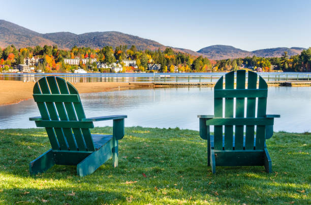 adirondack chairs on the shore of lake on a clear fall morning - lac mirror lake photos et images de collection