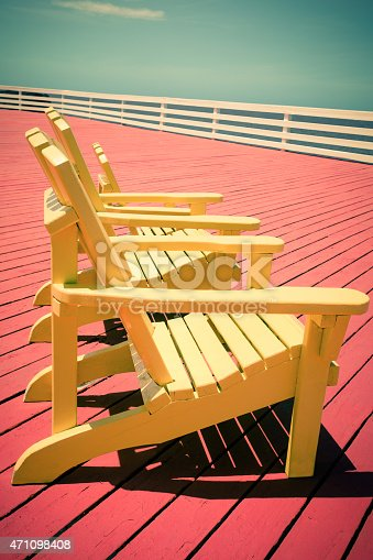 Vintage toned image of three yellow adirondack chairs on red deck