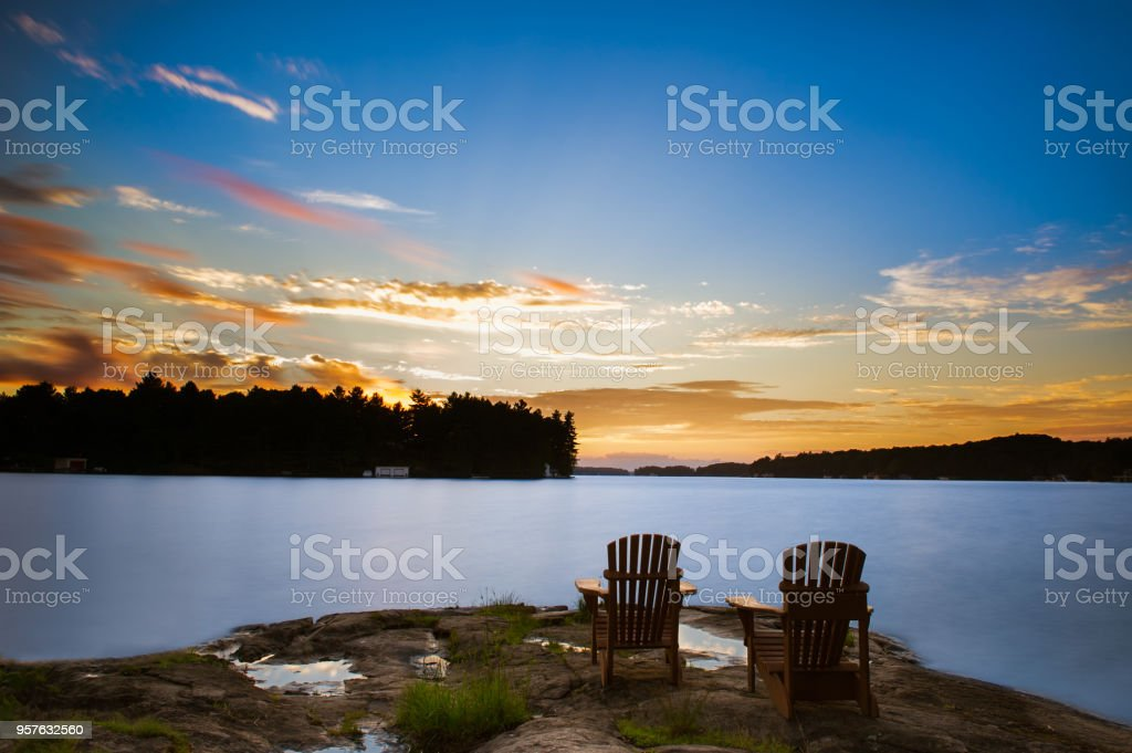 Adirondack chairs sitting on a rock at sunset stock photo