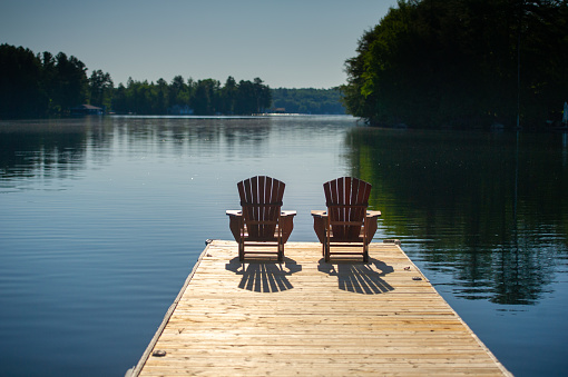 Two Adirondack chairs sitting on a wooden pier facing the calm water of a lake in Muskoka, Ontario Canada. A cottage nestled between trees is visible in background.