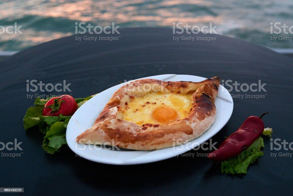 Adjarian khachapuri with eggs on table - Zbiór zdjęć royalty-free (Abchazja)