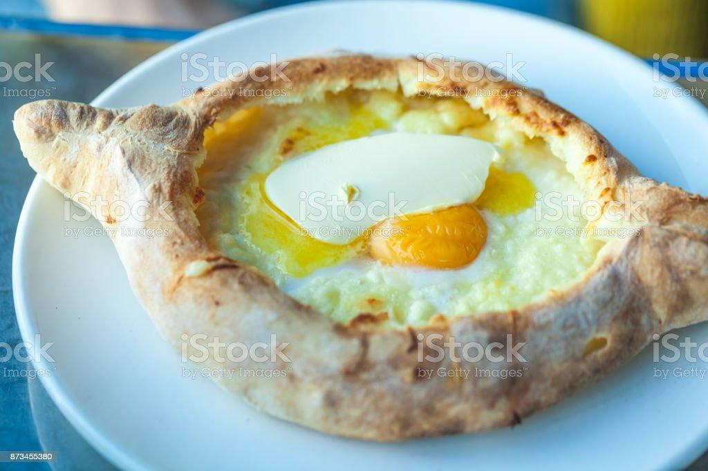 Adjarian khachapuri with eggs on the table stock photo