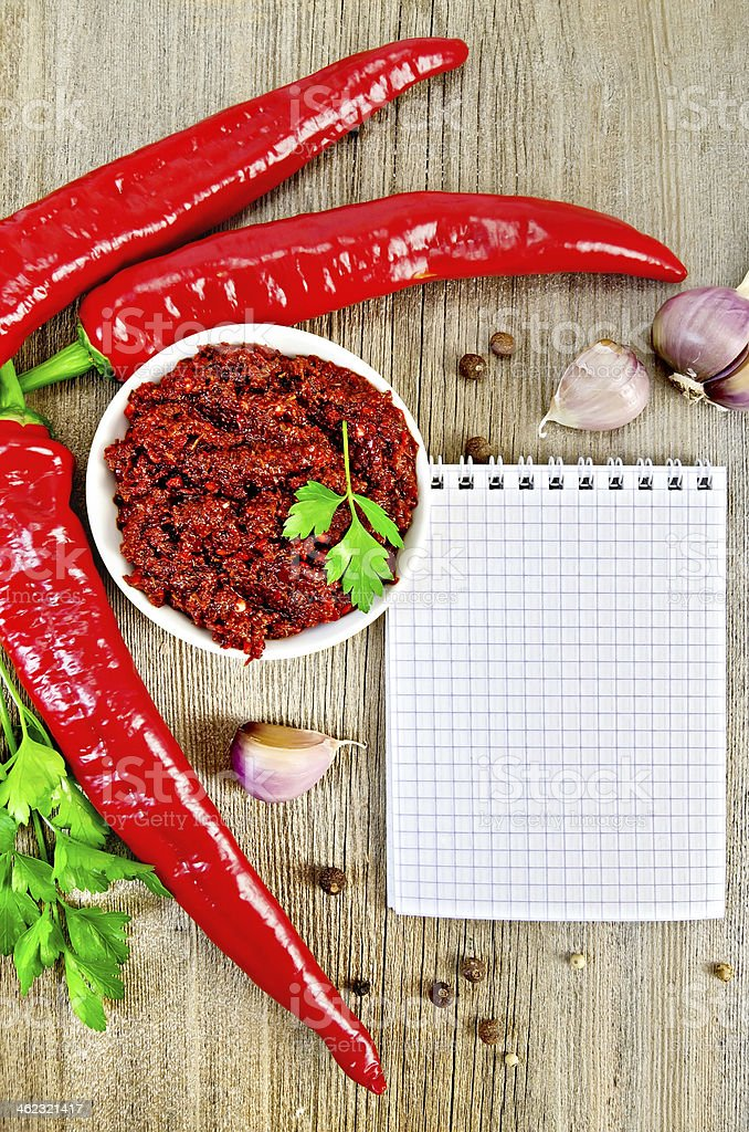 Adjika with fresh chili peppers and a notepad stock photo
