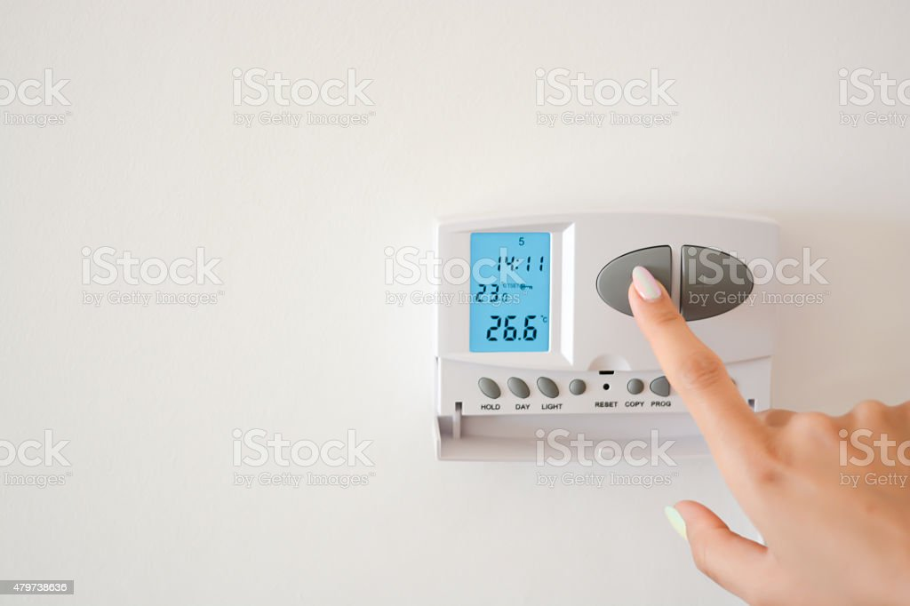 Adjust temperature with thermostat in home interior stock photo